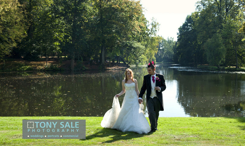 Bride and groom stroll by the lake at Hedingham Castle