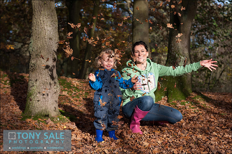 Mother & son play in leaves