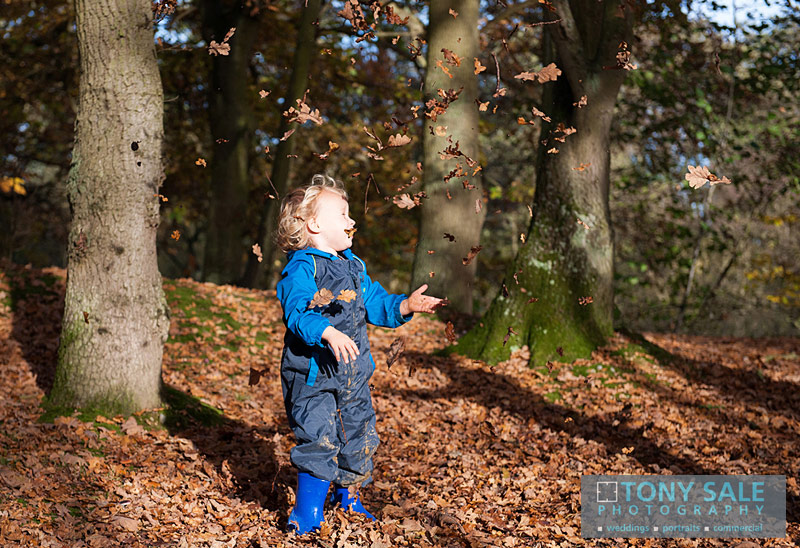 Young boy has fun throwing piles of leaves
