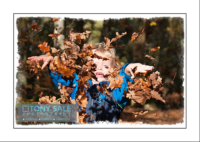 Such great fun - young boy plays in fallen leaves