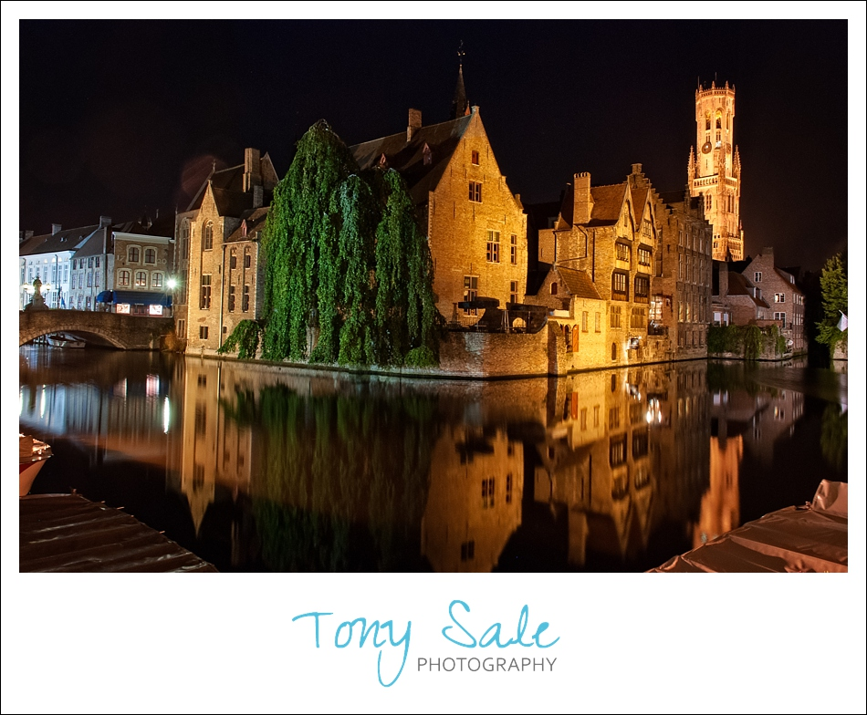 The Belfry of Bruges photographed at night and reflecting in the water.