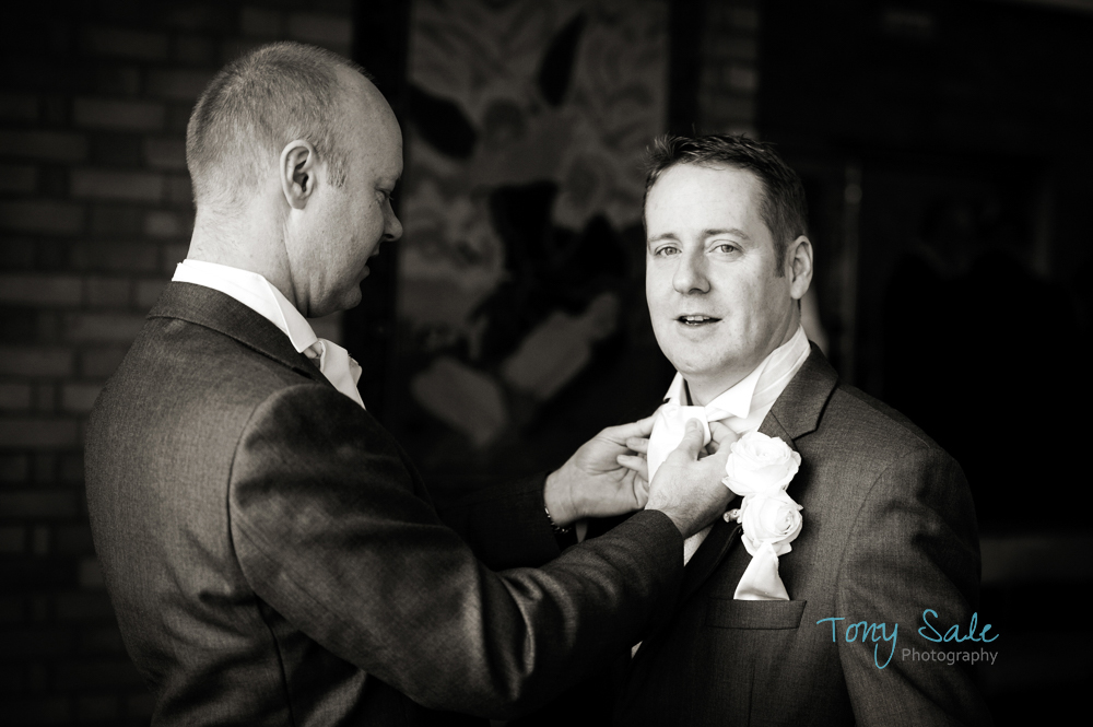 Best man helps the groom check his dress