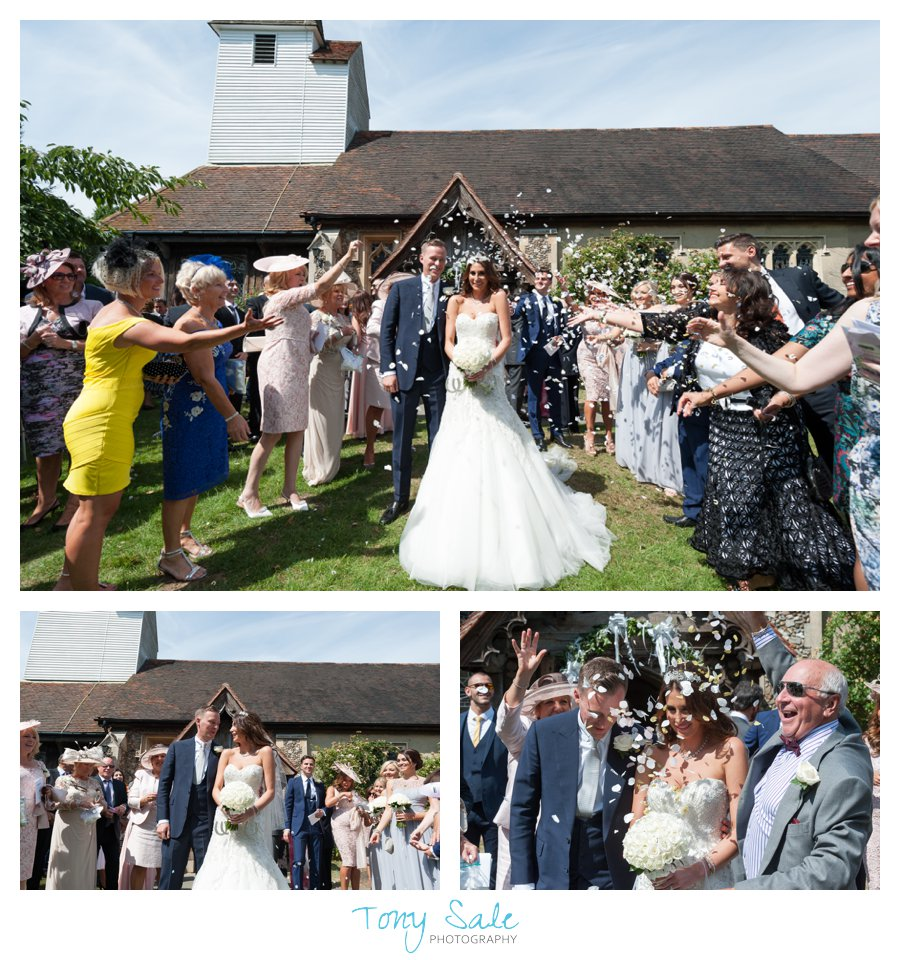 Bride and groom showered with confetti oside All saints Church